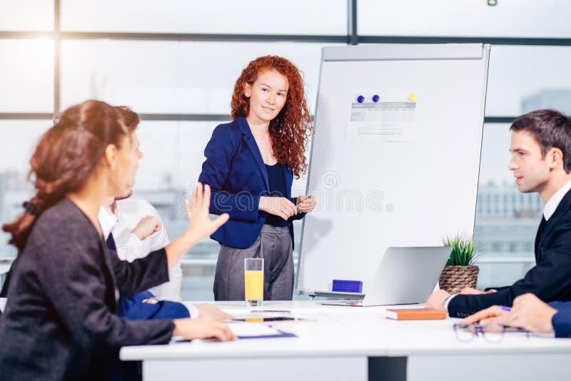 给介绍的女商人同事在办公室 库存图片