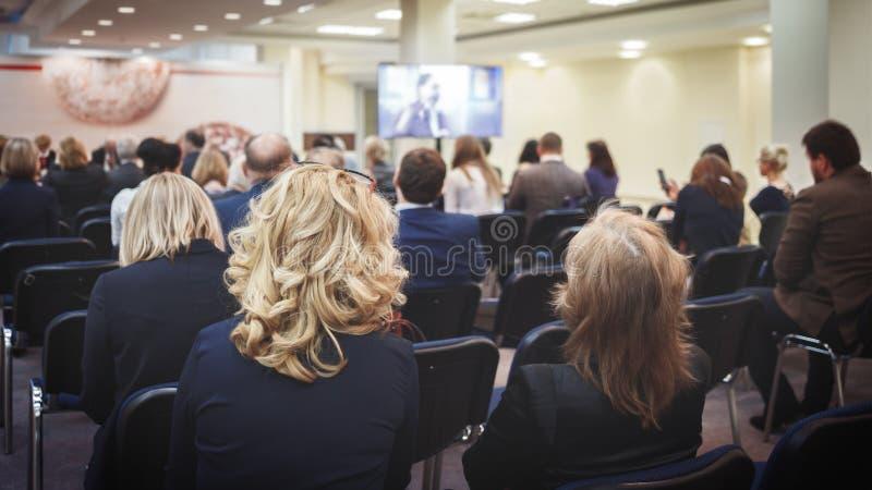 给介绍的女性报告人在教室里在大学车间 听lec的未被认出的参加者背面图  库存图片
