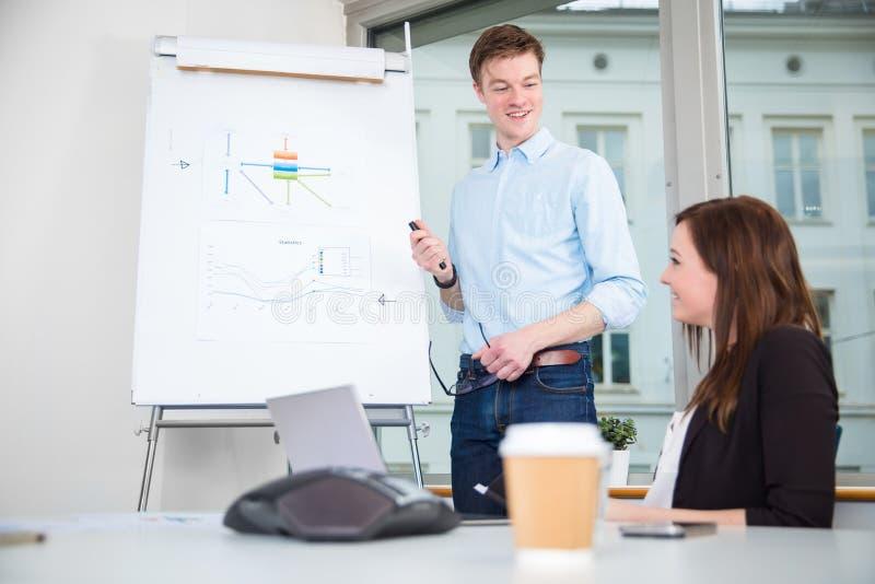 给介绍的微笑的商人同事在办公室 图库摄影