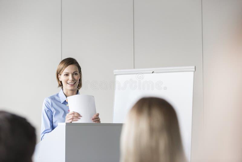 给介绍的微笑的女实业家会议的同事 库存图片