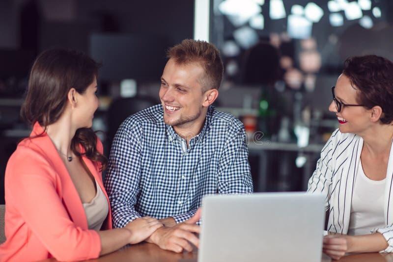 给介绍的投资顾问一对友好的微笑的年轻夫妇供以座位在她的书桌在办公室 库存图片