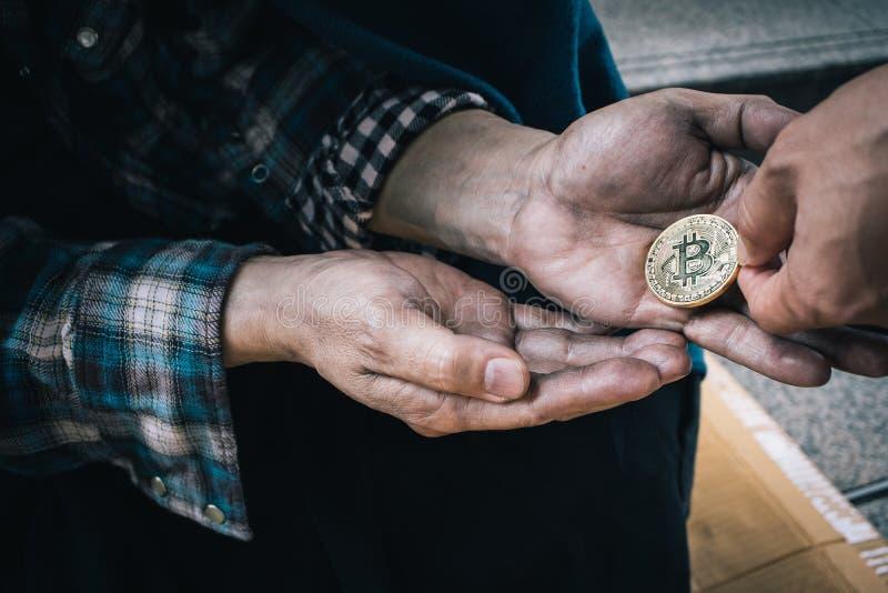 给从人类善良本性的男性叫化子手硬币,无家可归者在城市 免版税库存图片