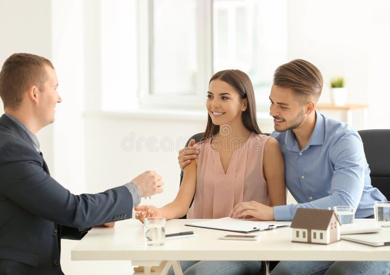 给从新房的不动产房地产经纪商钥匙年轻夫妇在办公室 免版税库存图片