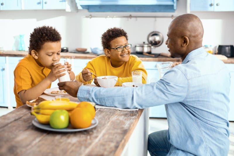给他的儿子每杯牛奶的有同情心的年轻父亲 图库摄影