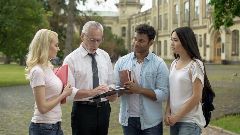 给任务的教授小组不同种族的学生,教育 图库摄影