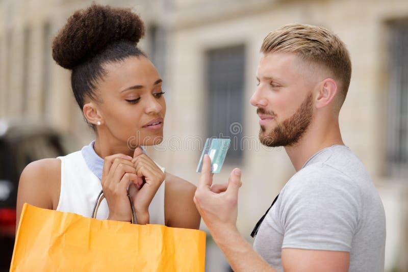 给信用卡的人女朋友 免版税图库摄影