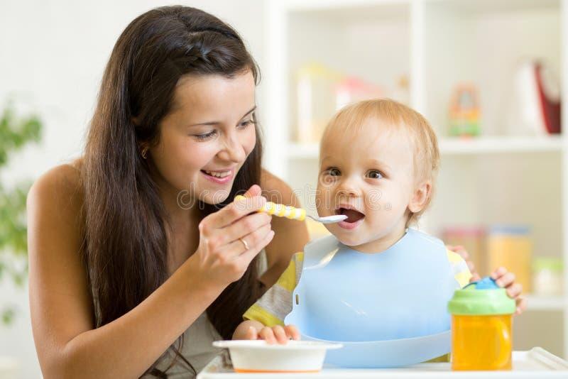 给健康食物的妈妈高脚椅子的小儿子在厨房里 免版税库存照片