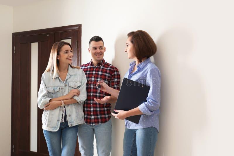 给公寓钥匙的不动产房地产经纪商年轻夫妇 免版税库存图片