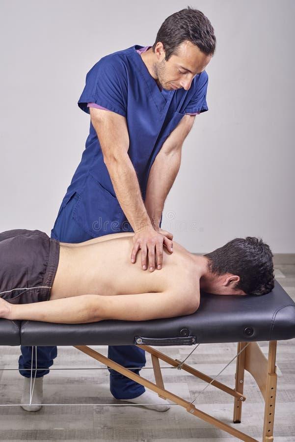 给后面按摩的生理治疗师 按摩脊柱治疗者,整骨疗法,手工疗法,针压法 库存照片