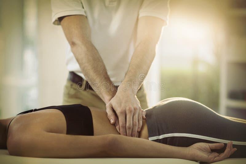 给后面按摩的男性生理治疗师女性患者 库存照片