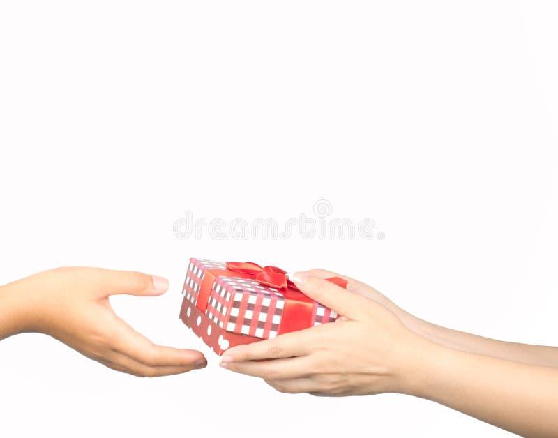 给和接受圣诞节礼物盒的特写镜头手包裹与红色丝带 库存图片