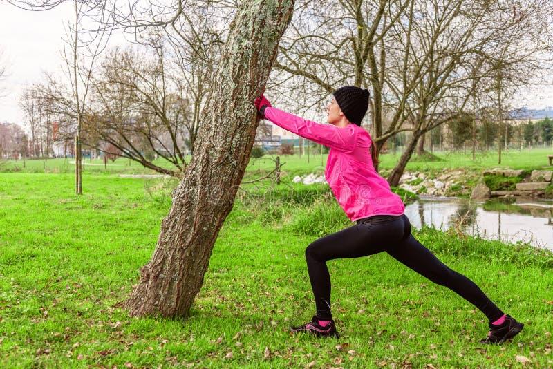 给和舒展腿加热的少妇在跑前在一个冷的冬天,秋天秋天天在都市公园 免版税库存照片