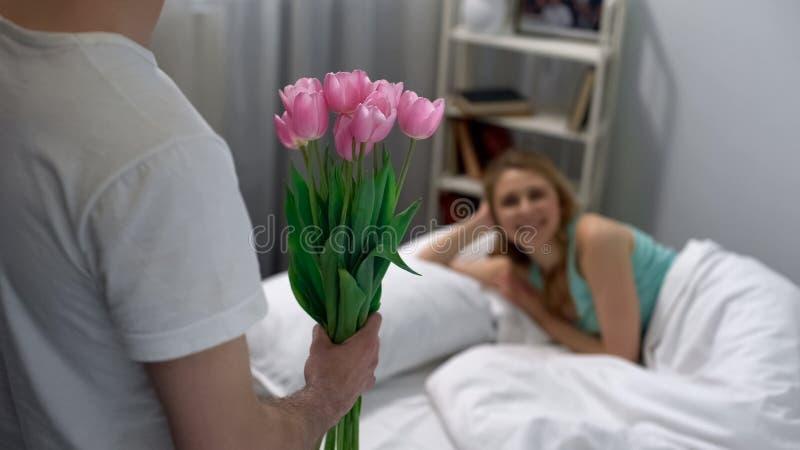 给困妻子的年轻丈夫郁金香在早晨,花交付 免版税库存照片