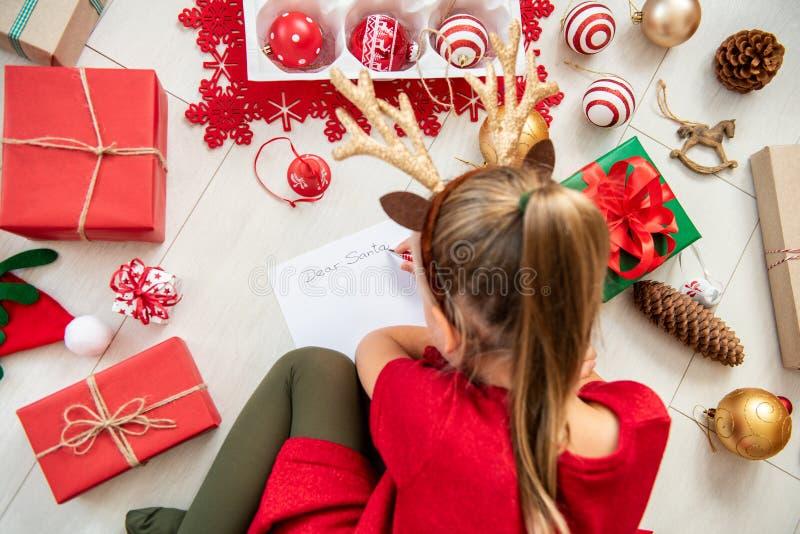 给圣诞老人的逗人喜爱的女孩文字信件在客厅地板上 写她的圣诞节wishlist的顶上的观点的少女 库存照片