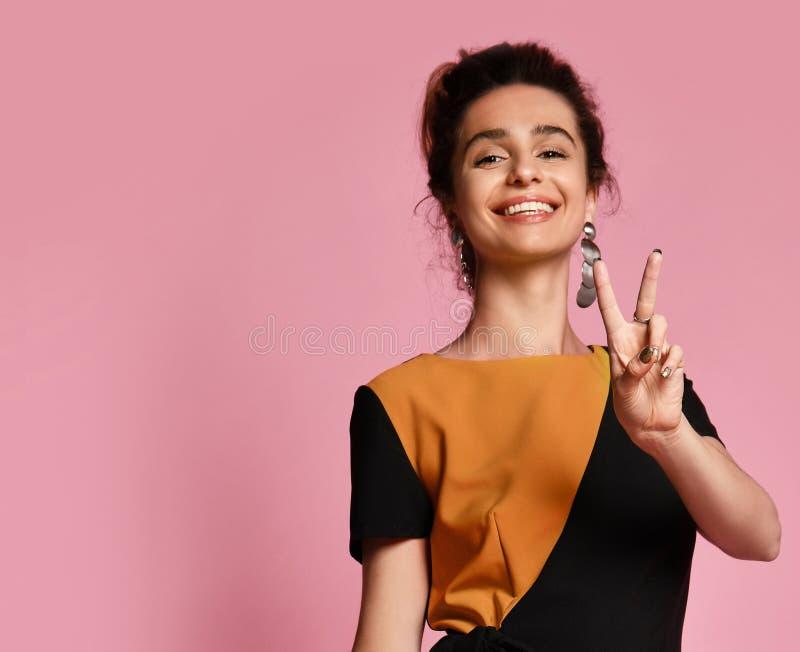 给在桃红色背景的年轻女人和平标志 免版税库存图片