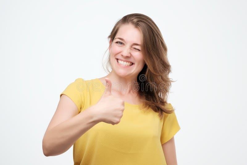 给在白色背景的愉快的少妇赞许 免版税库存照片