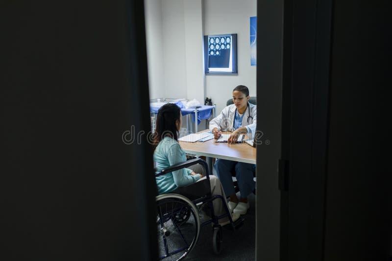 给处方的女性医生残疾女性患者在书桌 免版税库存照片