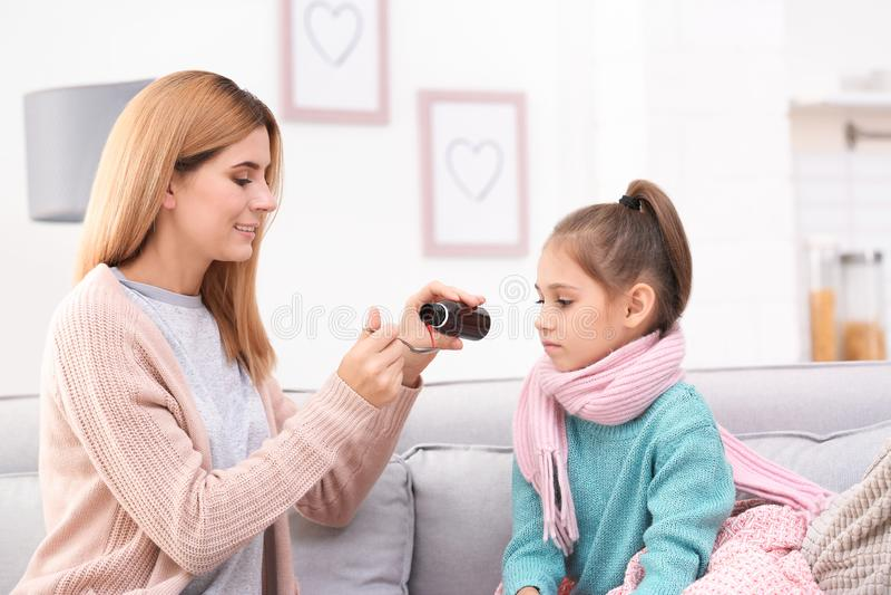 给女儿在沙发的母亲咳嗽糖浆 库存图片