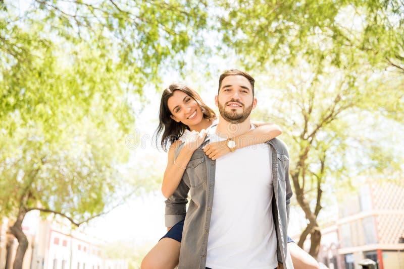 给女朋友肩扛乘驾的年轻人 免版税库存照片