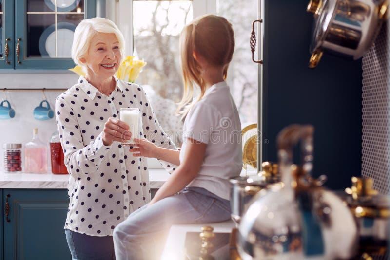 给她孙女杯牛奶的有同情心的祖母 免版税图库摄影