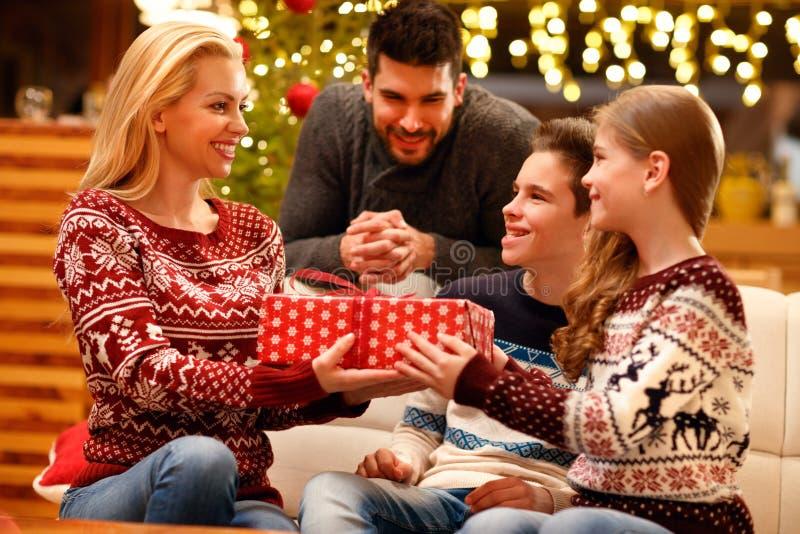给她爱恋的母亲圣诞礼物的激动的女儿 免版税库存照片