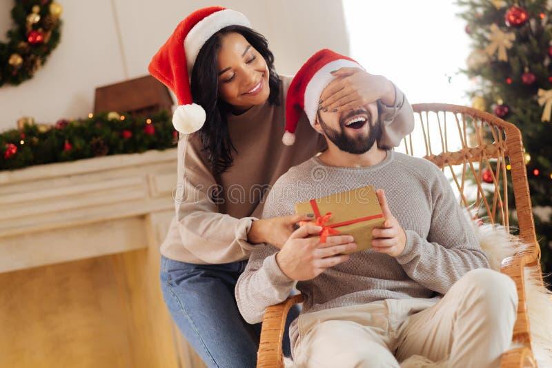 给她的丈夫圣诞节礼物的爱恋的妻子 库存图片