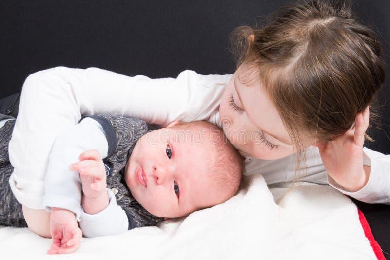 给她的小兄弟男孩在爱的姐妹拥抱和亲吻家庭 图库摄影