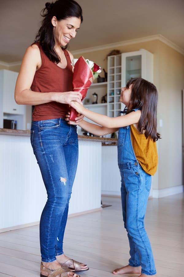给她的母亲一束花的年轻白女孩在Mother�s天,全长,水平 免版税图库摄影
