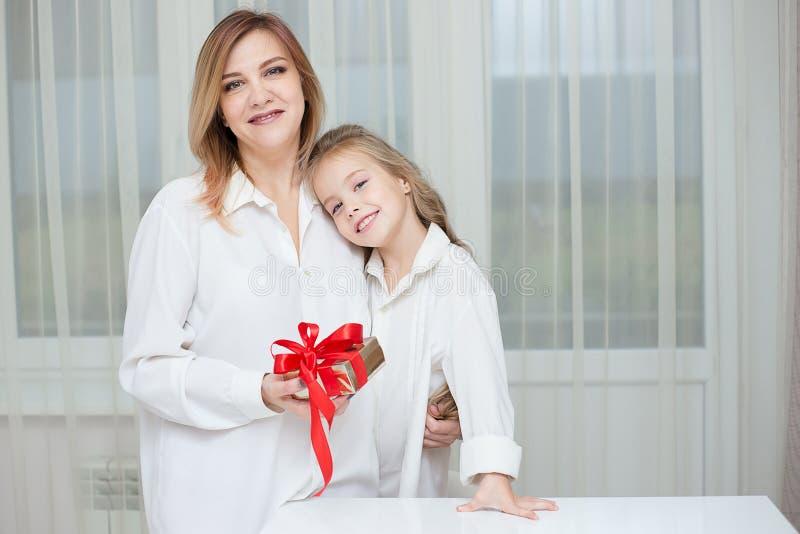 给她的母亲圣诞节礼物的女儿 免版税库存照片