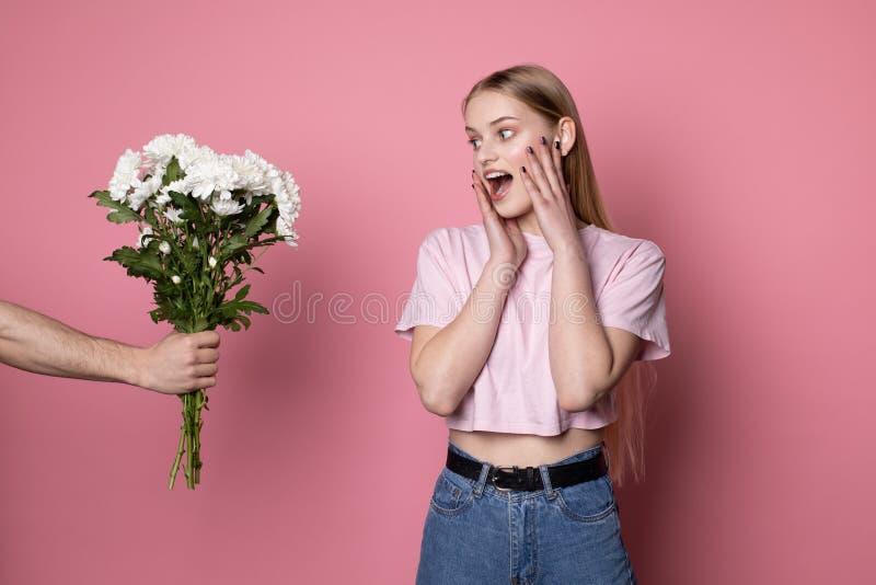 给她的男朋友的花有金发的愉快的美丽的年轻女性惊奇的 免版税库存照片
