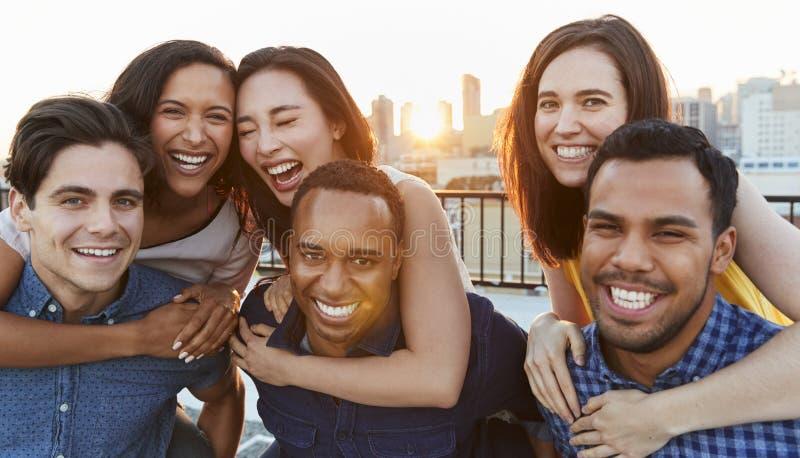 给妇女在屋顶大阳台的人画象肩扛与城市地平线在背景中 免版税图库摄影