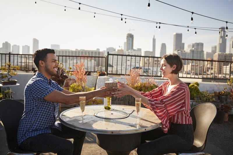 给妇女礼物的人,他们在与城市地平线的屋顶大阳台庆祝在背景中 免版税图库摄影