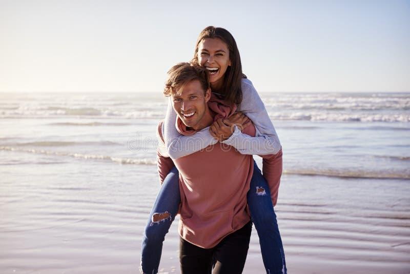 给妇女肩扛的人冬天海滩假期 免版税库存照片