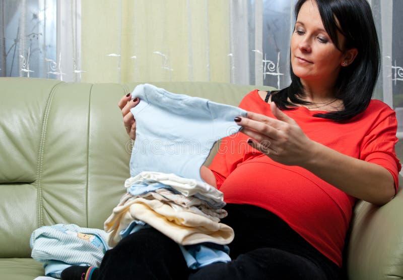 给孕妇穿衣 免版税库存图片