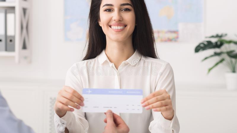 给对顾客的年轻旅行代理人机票 免版税库存图片