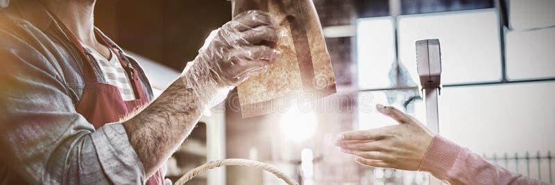 给小包面包的职员顾客 免版税图库摄影