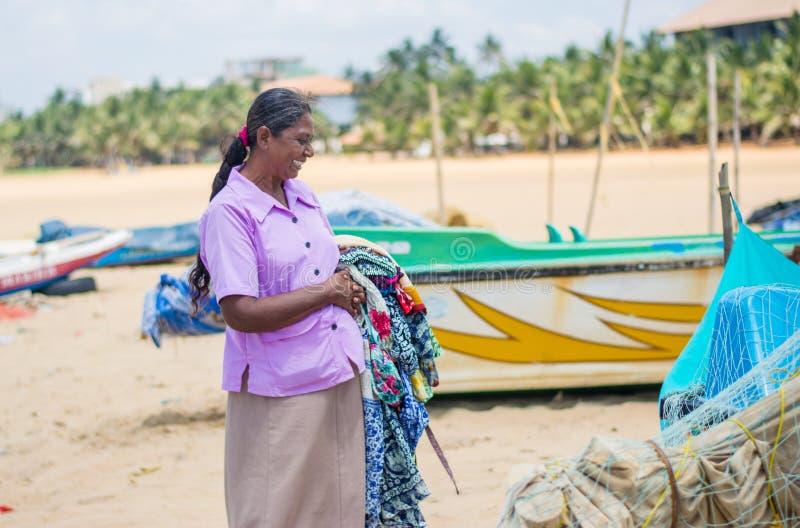 给微笑对海滩的女性供营商穿衣 免版税库存图片