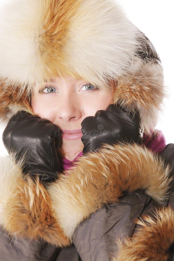 给微笑的冬天妇女穿衣 库存照片