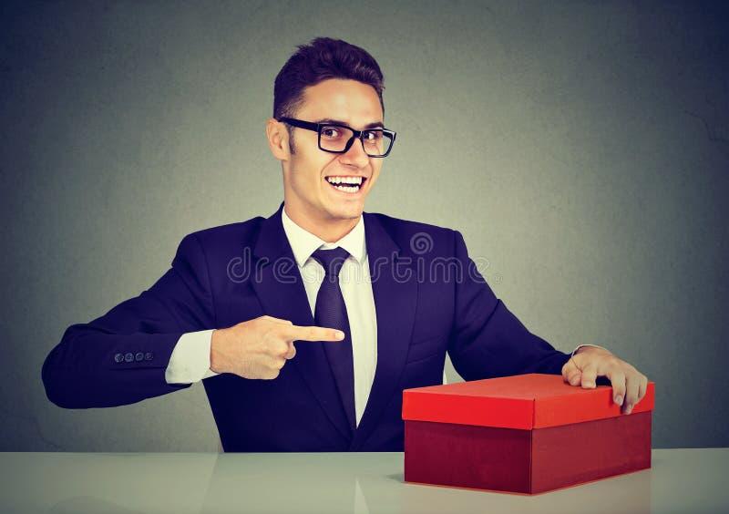 给微笑的推销员年轻的商人他的在红色箱子的产品做广告 免版税库存照片