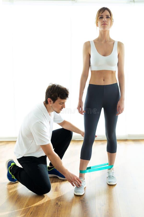 给忠告他的女性患者的年轻生理治疗师在身体训练期间在物理疗法屋子 库存图片