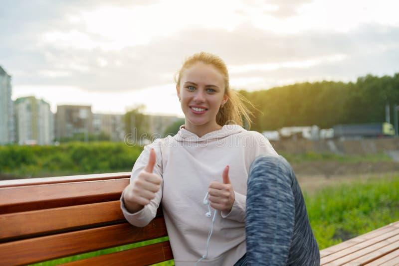 给成功的赞许标志女孩 一个愉快的微笑的大力士的画象在体育衣裳穿戴了 焦点 免版税库存照片