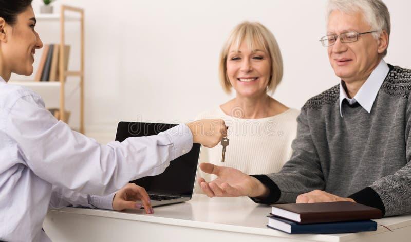 给成熟夫妇钥匙的地产商新房 免版税库存图片