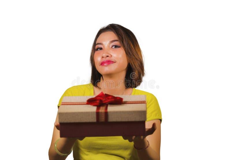给或接受圣诞礼物或有红色的年轻愉快和美丽的亚裔印度尼西亚妇女画象生日礼物箱子 免版税库存图片