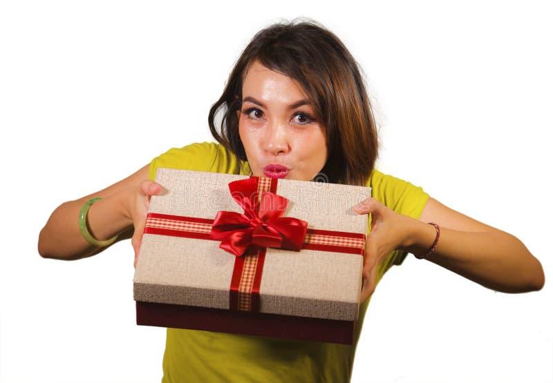 给或接受圣诞礼物或有红色的年轻愉快和美丽的亚裔印度尼西亚妇女画象生日礼物箱子 库存照片