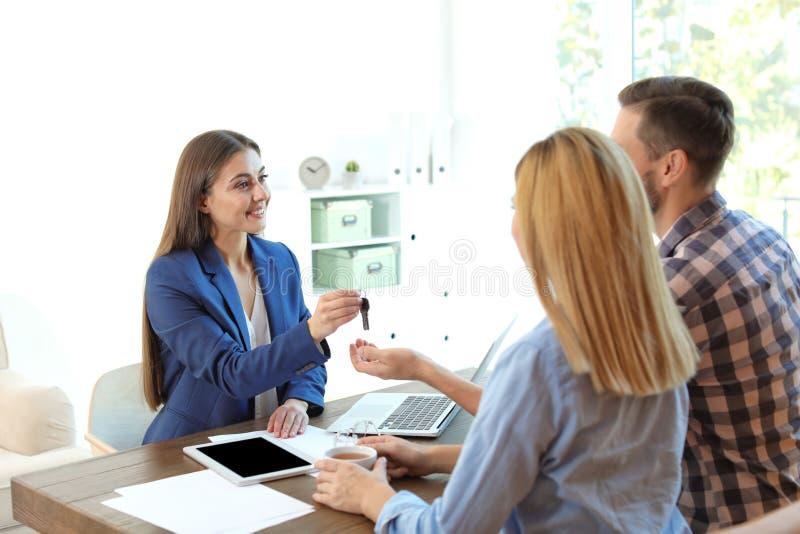给房子钥匙的女性不动产房地产经纪商结合 免版税库存图片