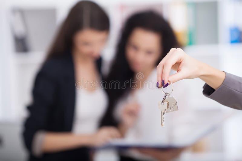 给房子钥匙的房地产开发商顾客 免版税库存照片