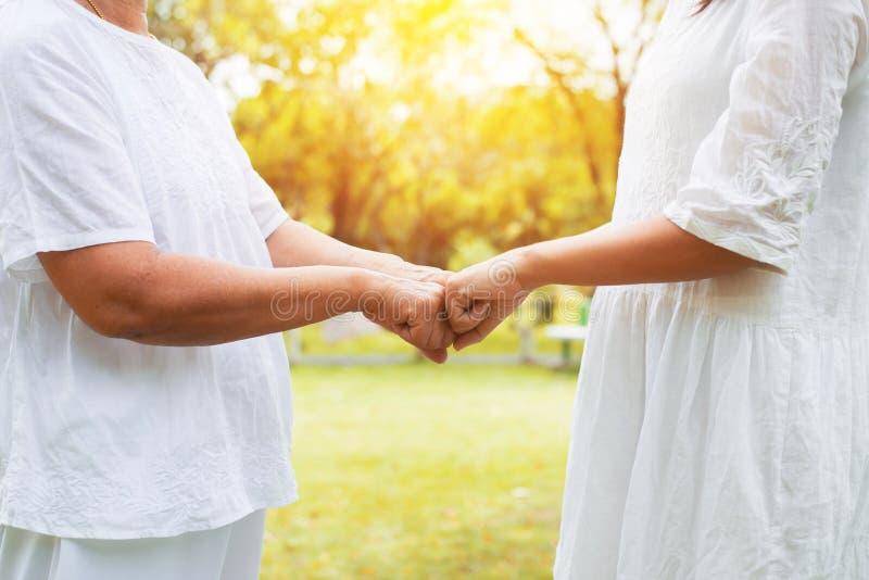 给拳头爆沸的亚裔妇女老人的手手年轻女人在室外在日落 免版税库存图片