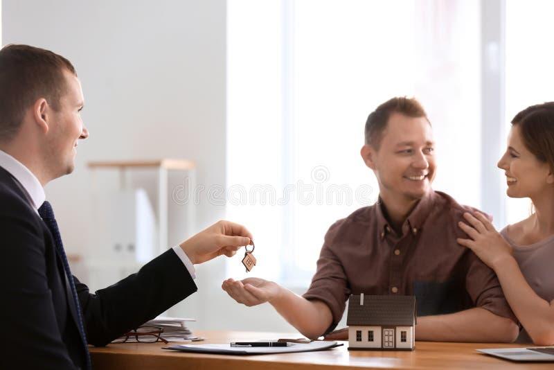 给新房的钥匙不动产房地产经纪商愉快的夫妇在办公室 图库摄影