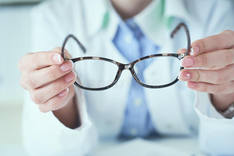 给新的玻璃的女性眼镜师手测试的和尝试的特写镜头的顾客 有客户比较的眼科医生 库存照片