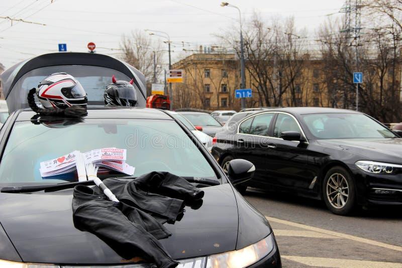给旗子、两件摩托车盔甲、一件摩托车夹克和交通鞭子做广告在一辆汽车的敞篷在路 免版税库存图片